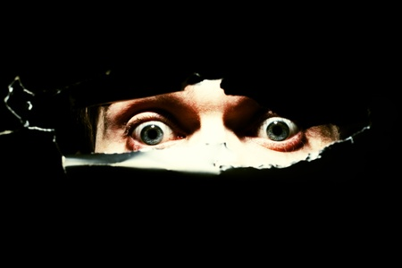 eye hole: Scary eyes of a man spying through a hole in the wall