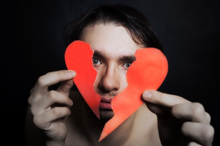 Face of young handsome man with broken paper heart closeup Imagens