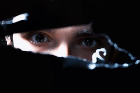 Eng ogen van een man spionage door een gat in de muur