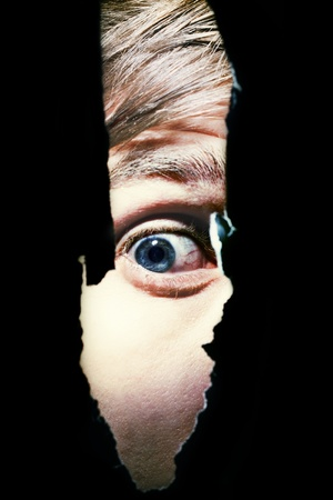 horror movies: Scary eyes of a man spying through a hole in the wall
