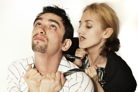 strangulation: woman with an artificial mustache strangling a young man tie on a white background
