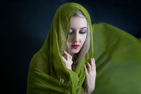 studio portrait of beautiful young woman in green summer shawl photo
