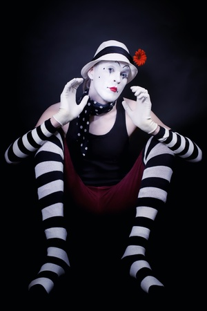 Studio portrait of Dramatic funny mime in white hat with red flower and striped gloves sitting on floor on black background photo
