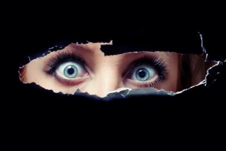 Blauwe ogen vrouwen spionage door een gat Stockfoto