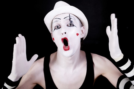 Theater funny mime with open mouth in white hat on black background photo