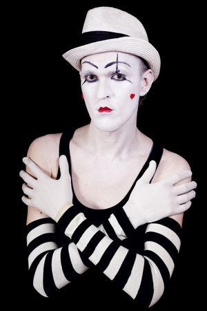Studio portrait of serious theatrical clown in white hat and striped gloves with red hearts on her face isolated on black background photo