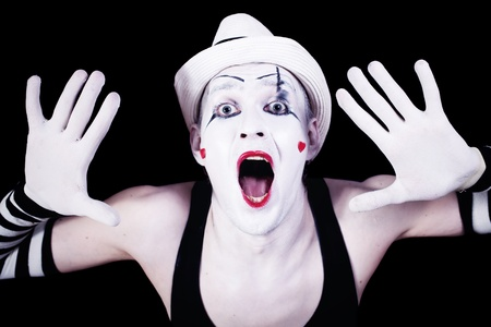 Funny screaming mime in white hat isolated on black background photo