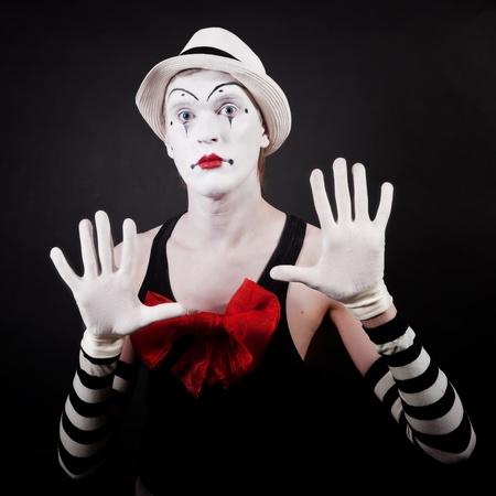 m�mica: Retrato de un actor de teatro en mime divertido de maquillaje con un lazo rojo en el pecho de sombrero blanco y guantes rayas sobre un fondo negro