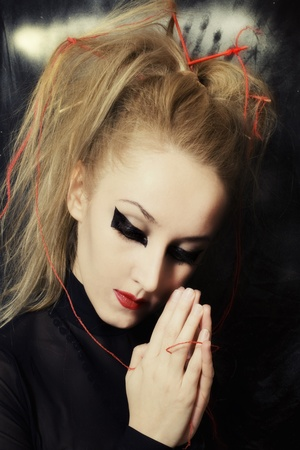 Portrait of beautiful young Caucasian woman with makeup in Gothic style, and his hands clasped in prayer photo