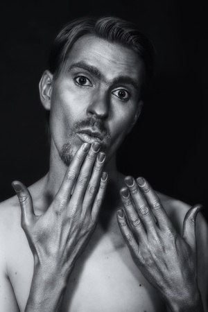 monochrome portrait of young attractive man with a silvery makeup on her face and hands against a black background photo