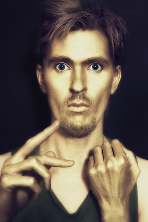 studio portrait of young attractive blue-eyed men with gold makeup on her face and hands against black background photo