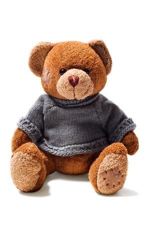 Toy brown teddybeer met patches in groene trui geïsoleerd op witte achtergrond