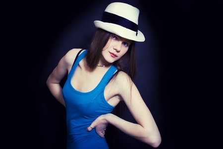 portrait of young blue-eyed girl in white hat on black background photo