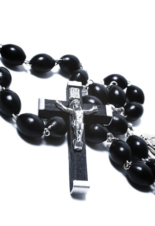 Catholic black wooden beads with metal crucifix isolated on white background photo