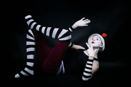 pantomime: Studio portrait of Dramatic funny mime in white hat with red flower and striped gloves lying on floor on black background