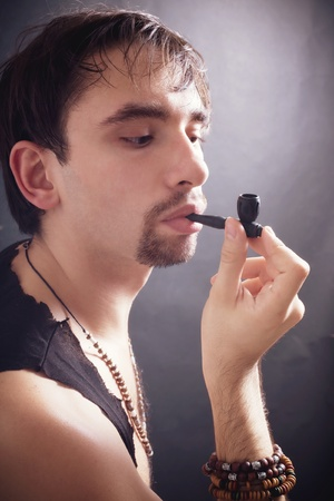 young man smoking little pipe on black background Stock Photo - 9097682