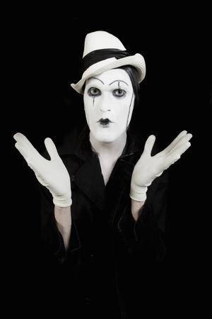 pantomima: cara y manos de mime con maquillaje oscuro sobre fondo negro