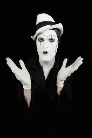 face and hands of mime with dark make-up on black background photo
