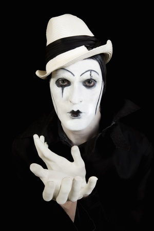 face and hands of mime with dark make-up on black background Imagens