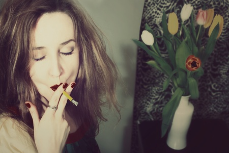 beautiful young woman smokers with a bouquet of tulips in a vase photo