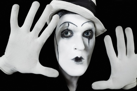 mimo: cara y manos de mime con maquillaje oscuro sobre fondo negro