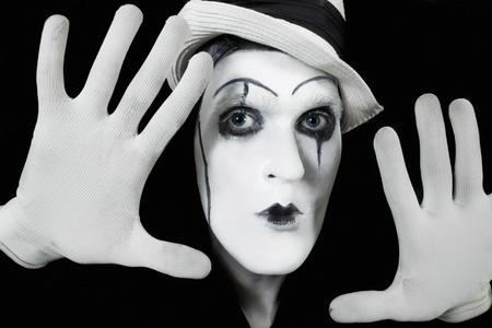 gezicht en de handen van mime met donkere make-up op zwarte achtergrond