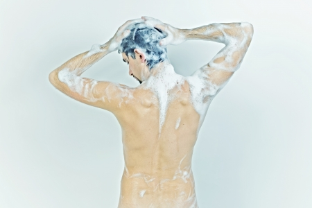 Young naked man taking a shower in the foam with a beautiful body on white background photo