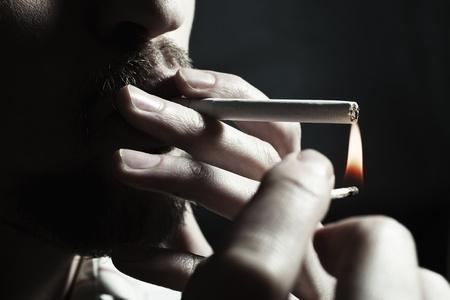 Men's hand lights a cigarette with a match closeup