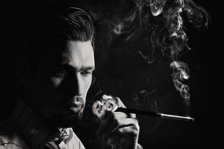 Studio portrait of a young man smoking a cigarette on a black background Imagens - 9553667