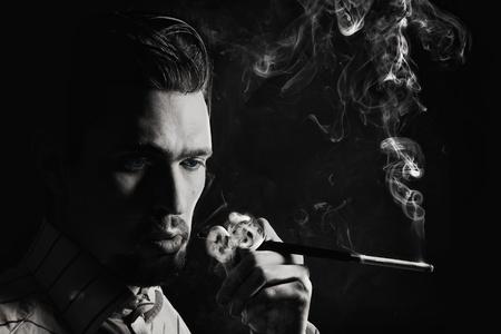 Studio portret van een jonge man roken van een sigaret op een zwarte achtergrond Stockfoto