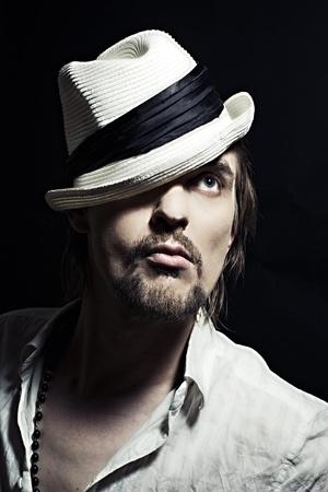 studio portret van knappe jonge man in witte hoed op zwarte achtergrond close-up