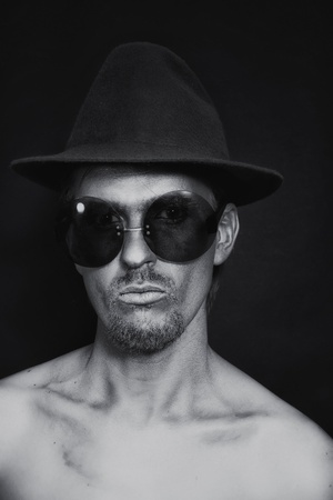 Portrait of young man with the silver make-up in a hat and sunglasses on a black background photo