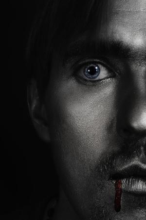 Halve gezicht portret van jonge man met zilver verf op zijn gezicht en bloed aan zijn lip-closeup Stockfoto