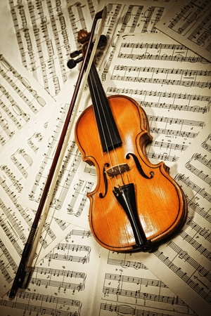Old wood violin lying on musical notes closeup photo