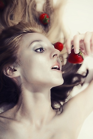 beautiful fair woman with silver makeup eating strawberries photo