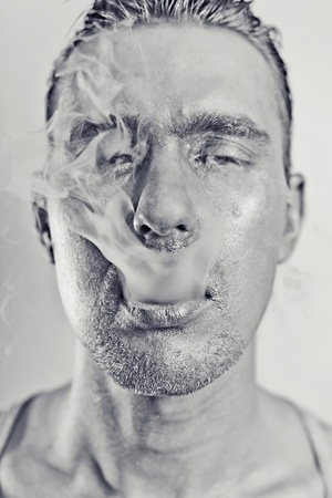 monochrome portrait of young attractive man with a silvery makeu in the smoke photo