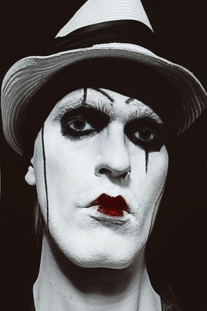 face  of mime with dark make-up on black background closeup photo