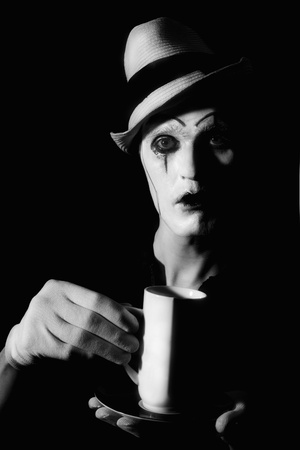Portrait of  terrible mime clown holding white cup photo