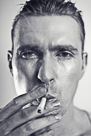monochrome portrait of young attractive man with a silvery makeup  with cigarette photo