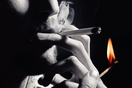 Mens hand lights a cigarette with a match closeup
