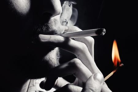 smoking a cigarette: Mens hand lights a cigarette with a match closeup