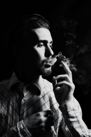 and the horizontal man: Studio portrait of a young man smoking a cigarette