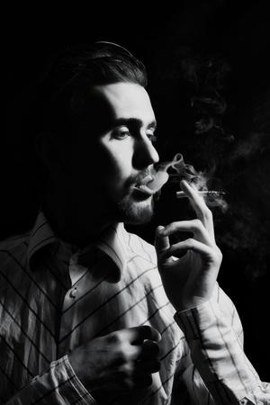 Studioportret van een jonge mens die een sigaret rookt