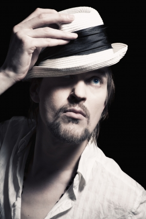 black head and moustache: Studio portrait of a handsome young man with a white hat in hand on a black background Stock Photo