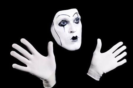 Mime face and hands in white gloves and a theatrical make-up isolated on black background photo