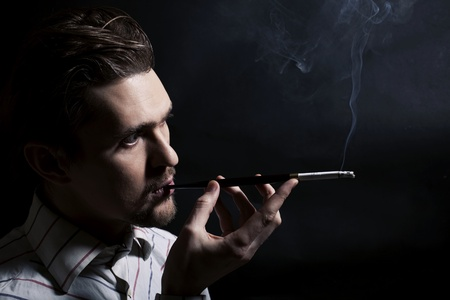 Studio portrait of a young man smoking a cigarette on a black background Stock Photo - 10119527