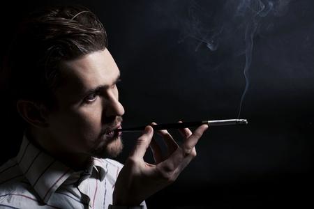 Studio portret van een jonge man een sigaret te roken op een zwarte achtergrond