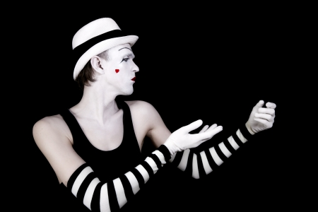 dancing mime in white hat with  heart on her cheek on black background