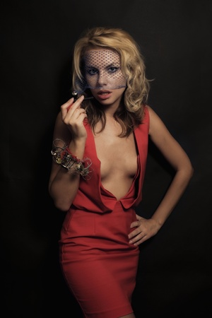 Young beautiful blonde woman in a red dress and veil in with a pipe on black background photo