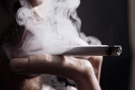 man close up: fumo di sigaretta nella mano di giovane uomo vicino Archivio Fotografico